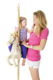 Playful on the Carousel Horse. An adorable 2-year-pld and her mom having fun with the carousel horse.  On a white background Stock Photography