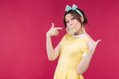 Playful charming young woman pointing on bubble gum balloon Stock Image