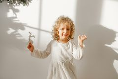 Playful cheerful little beautiful girl with blonde curly hair plays with toy deer, dressed in festive white dress, ready stock photo