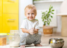 Playful child boy with face in flour surrounded Stock Images
