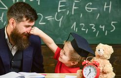 Playful child concept. Kid cheerful play with dad. Father with beard, teacher teaches son, little boy, while child. Pinching his nose. Teacher and pupil in royalty free stock photography