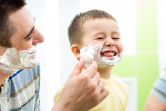 Playful child and father shaving together at home bathroom