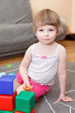 Playful child on floor with toys Stock Photo