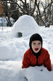 Playful Child and Igloo. A young child is playing in the snow in front of a freshly built igloo Royalty Free Stock Photos