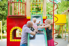 Playful child with parents at the playground outdoor Stock Image