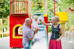Playful child with parents at the playground outdoor Royalty Free Stock Photo