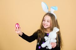 Playful child with soft toy. Meet spring holiday. Easter egg hunts as part of festival. Girl little child easter bunny. Accessory hold dyed egg. Origin of stock images