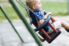 Playful child on swing outdoors. Shot from the side royalty free stock image