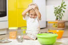 Playful child boy with face in flour surrounded kitchenware and foodstuffs. Playful child toddler with face soiled flour. Little boy surrounded kitchenware and royalty free stock photo
