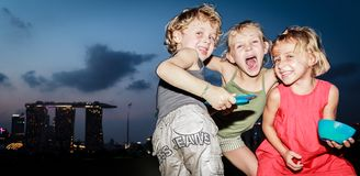 Playful children playing and posing funnily at Marina Barrage, Singapore royalty free stock photo