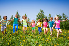 Playful children run, hold hands in green field. Playful children run and hold hands in green meadow during summer Royalty Free Stock Photos
