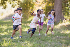 Playful children running at campsite. Playful children running on grassy field at campsite stock photography
