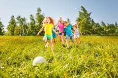 Playful children running to the ball in field Royalty Free Stock Images