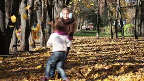 Playful children. Two little girls spinning in autumn park stock footage