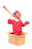 Playful clown coming out of a box and holding a horn and a prese Stock Photography