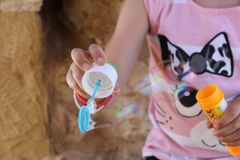 Playful and colorful girl playing with soap bubbles Royalty Free Stock Photography