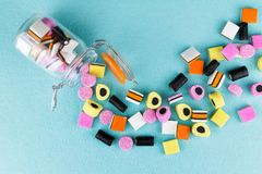 Playful, colorful pile of candy liquorice allsorts spilling from jar royalty free stock image