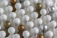 Gold, Silver and Bronze game pieces in a crowd of white pieces royalty free stock photography