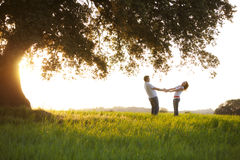 Playful couple. Young playful couple under huge tree at sunset