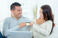 Playful couple arguing over on-line shopping royalty free stock photos