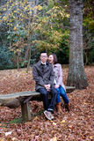 Playful couple in autumn. Playful couple sitting on a park bench with autumn colors stock images