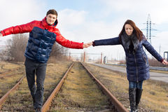 Playful couple balancing on the railway tracks Royalty Free Stock Images