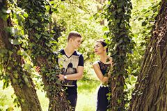 Playful couple behind trees in park Royalty Free Stock Image