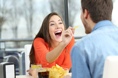 Playful couple eating chip potatoes. And joking looking each other in a date in a coffee shop Stock Image
