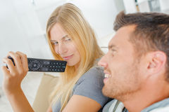 Playful couple fighting over TV remote Royalty Free Stock Photo