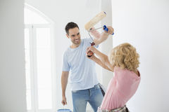 Playful couple fighting while painting new house Stock Images