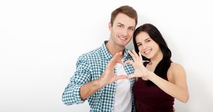 Playful couple fooling on valentine day. Beautiful young lovers are joining and smiling, making a heart frame from their royalty free stock image