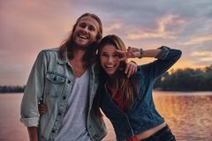 Playful couple. Happy young couple in casual wear smiling and looking at camera while standing near the lake stock photos