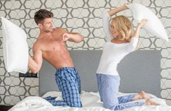 Playful couple having a pillow fight. Playful attractive young couple having a pillow fight as they kneel on their bed in their sleepwear smiling and laughing royalty free stock photos