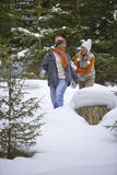 Playful couple holding hands in snowy woods stock photos