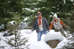 Playful couple holding hands in snowy woods stock images