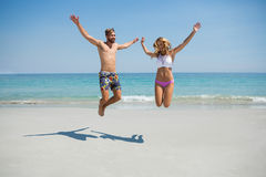 Playful couple jumping at beach Stock Photo
