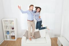 Playful couple jumping on sofa Stock Photography