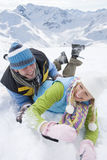 Playful couple laying in snow with mountain in background Royalty Free Stock Images