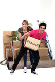 Playful couple moving house Stock Photos
