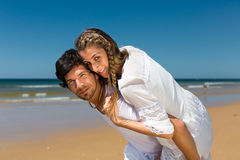 Couple enjoying freedom on the beach Stock Images