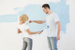Playful couple painting each other in new house Royalty Free Stock Photography