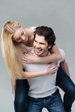 Playful couple riding piggy back together Royalty Free Stock Images