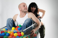 Playful couple with shopping cart Royalty Free Stock Photos