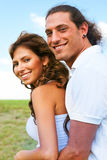 Playful couple smiling. Young man embracing female from back and smiling Stock Image