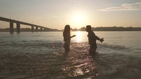 Playful couple spraying with water in the river. On a sunny evening. They get wonderful positive emotions stock video footage