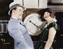 Playful couple standing on scale Royalty Free Stock Photos