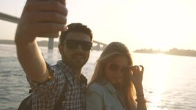 Playful couple taking photographs on the river bank stock footage