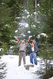 Playful couple throwing snow in woods Stock Photo