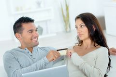 Playful couple about to spend money on-line stock photos