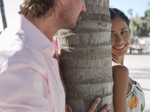 Playful Couple By Tree Trunk Royalty Free Stock Image